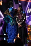 """THE MASKED SINGER: L-R: Peacock and host Nick Cannon in the """"All Together Now"""" episode of THE MASKED SINGER airing Wednesday, Feb. 13 (9:00-10:00 PM ET/PT) on FOX. Cr: Michael Becker / FOX."""